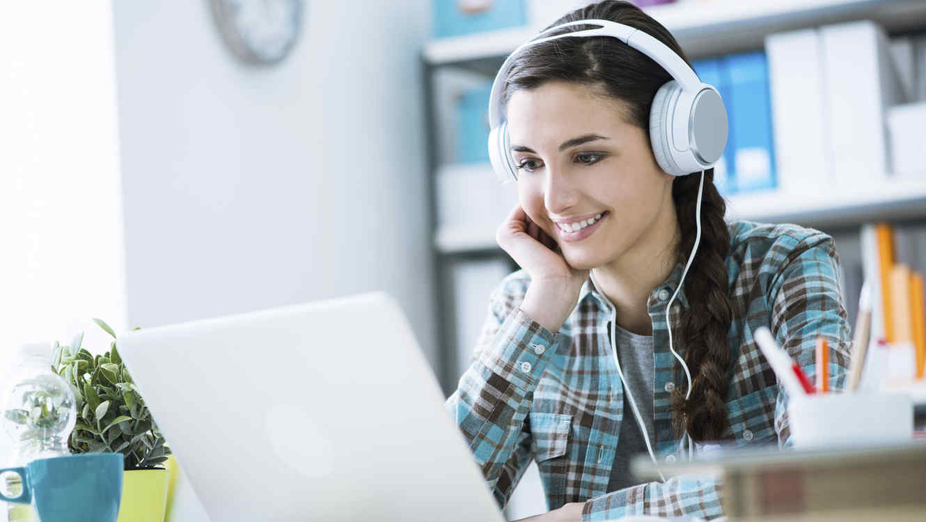 Girl with headphones using a laptop